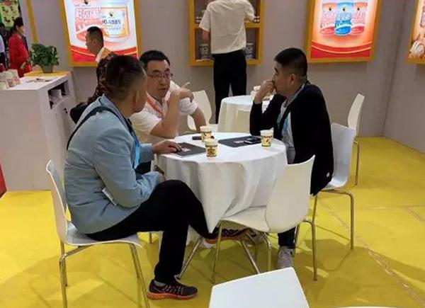 花帝美上美事业部销售总监张仁杰(中),向客人重点介绍HD速发蛋糕油、E6024香蕉油香精的适用范围及使用方法。