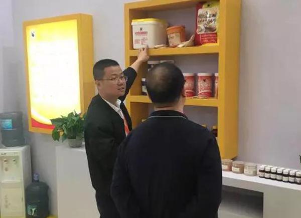 业务员周明华在向客人介绍牛乳香粉、速发蛋糕油等产品。