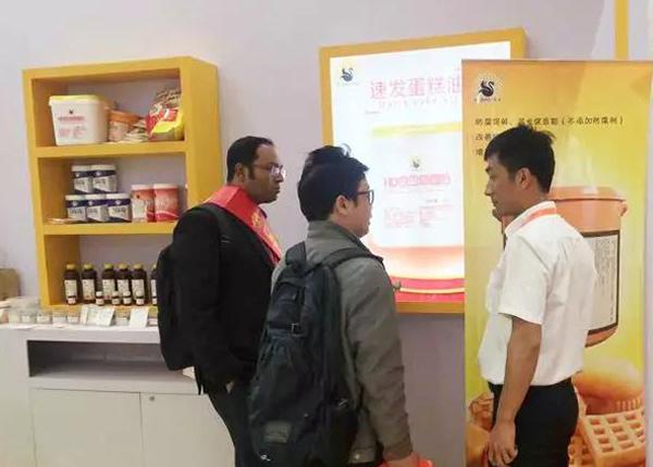 孟加拉国朋友也来参观花帝产品,业务员韩照磊向他们推荐特浓牛奶香粉、香乳素等产品。